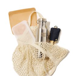 Flat lay image of all the products included in this zero waste on-the-go bundle. One orange sandwich stasher bag, one clear snack stasher, one stainless steel water bottle, one set of bamboo utensils, and a natural colored cotton string market bag.