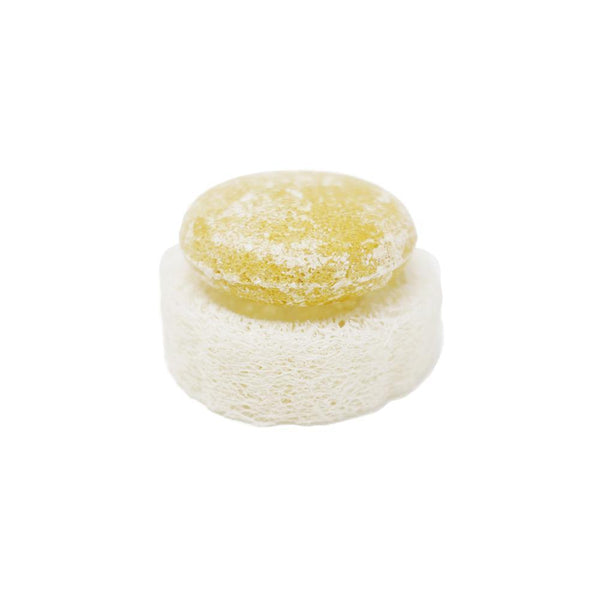product image of a round yellow shampoo bar sitting on top of a round zero waste and package free loofah.  The loofah is a natural white color.