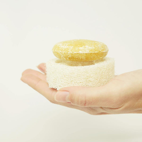 hand holding a round yellow shampoo bar that is sitting on top of a round zero waste loofah.  The loofah is a natural white color.