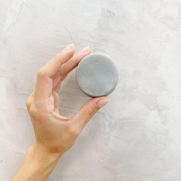 hand holding a package free light grey round peppermint tea tree conditioner bar