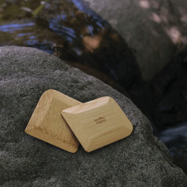 Two brown rectangular bamboo pot scrapers sitting on a rock beside a stream.