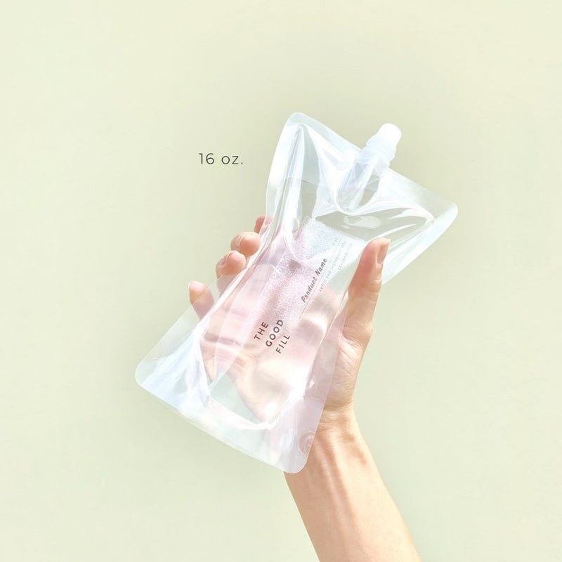hand holding a zero waste 16oz. clear bulk re-fill pouch for package free unscented conditioner