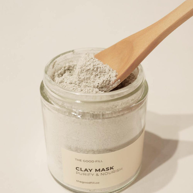Small brown wooden spoon scooping light weight mask powder from a 4oz. reusable Good Fill glass jar.