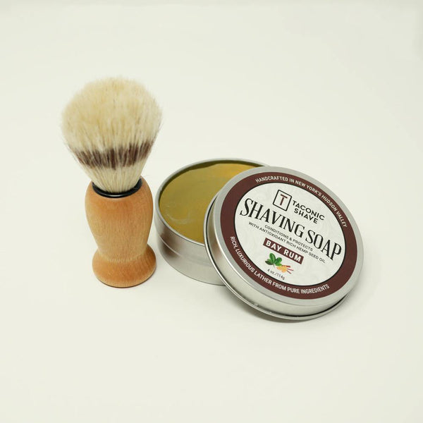 Product image of a shave brush sitting next to a round tin of shaving soap.