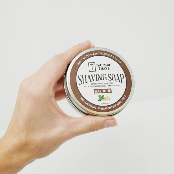 hand holding a round 4oz. tin of Bay Rum all natural shaving soap with a brown sticker label