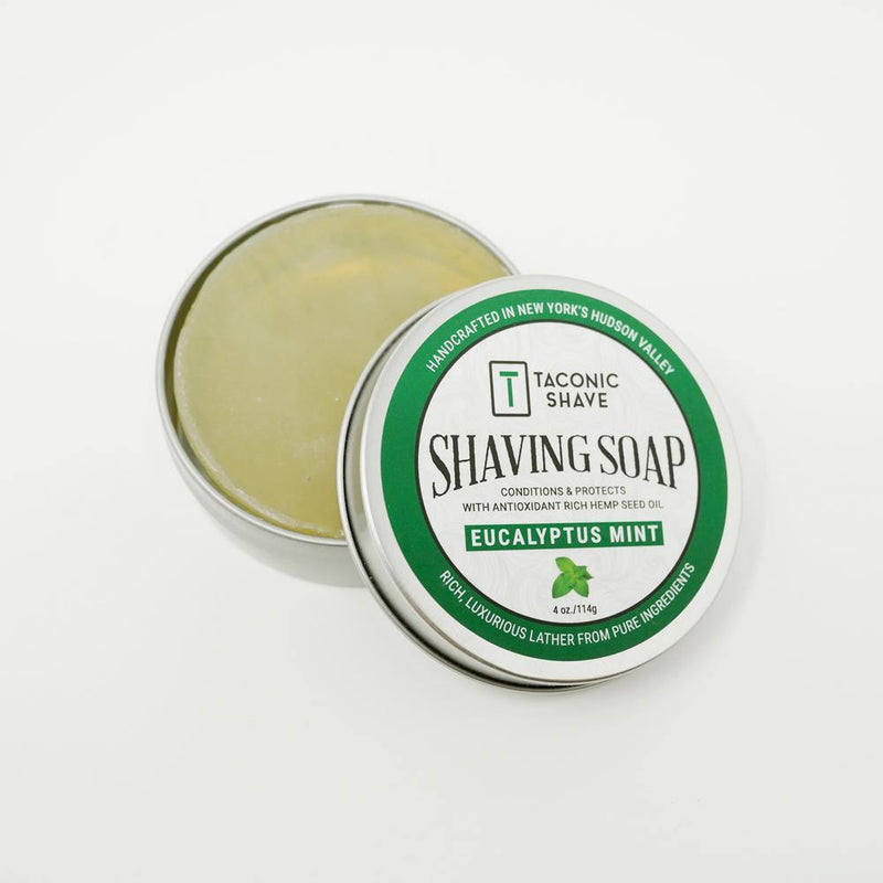 product image of a round tin of eucalyptus mint all natural shaving soap with the lid sitting to the side, showing the soap inside the tin. The tin lid has a green sticker label