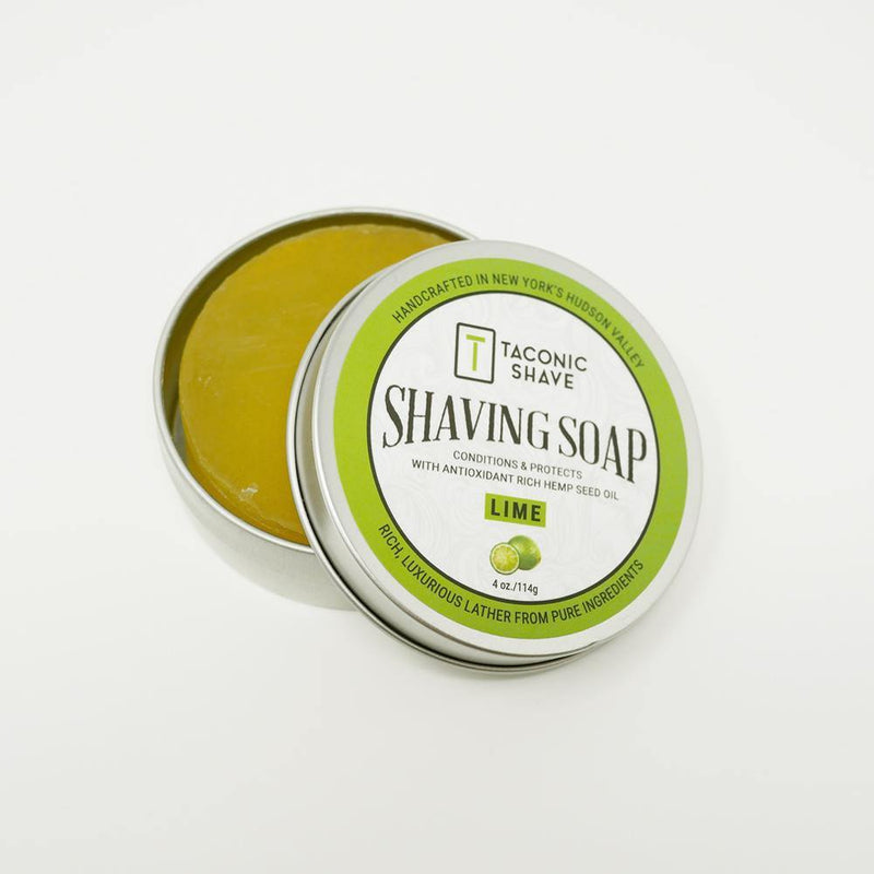 product image of a round tin of lime all natural shaving soap with the lid sitting to the side, showing the soap inside the tin. The tin lid has a lime green sticker label