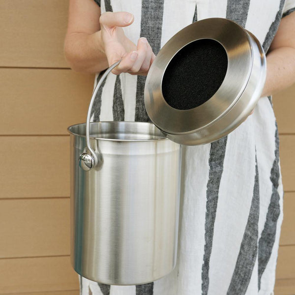 person holding a stainless steel compost bin in one and holding the stainless steel compost lid with a black filter in the other hand