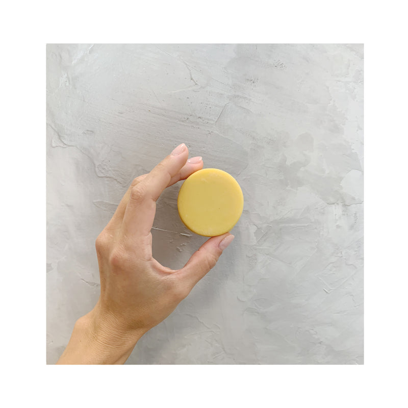 hand holding a yellow round zero waste sweet citrus conditioner bar