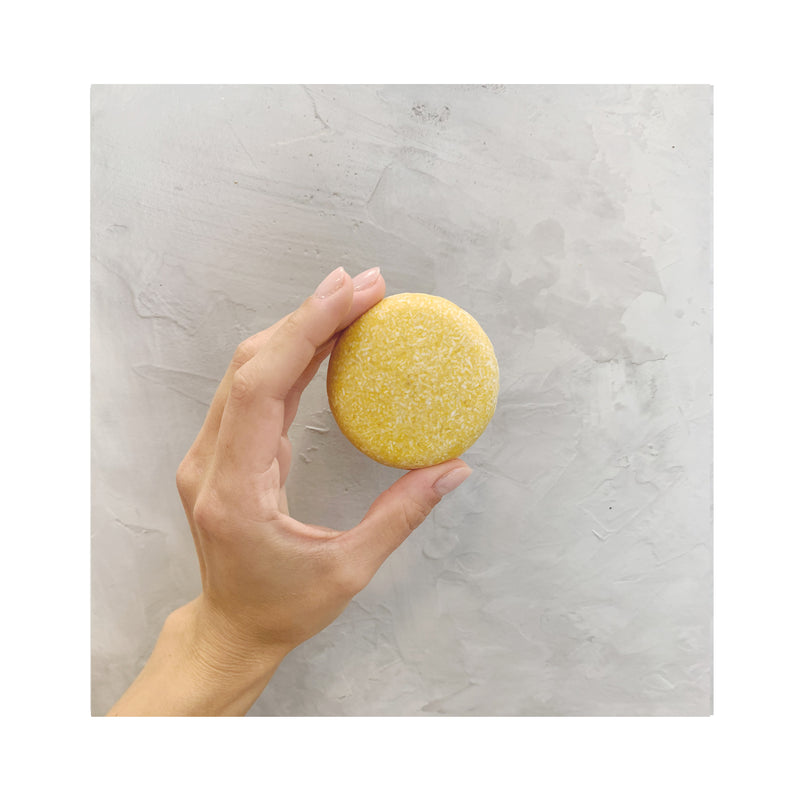 hand holding a yellow round zero waste sweet citrus shampoo bar