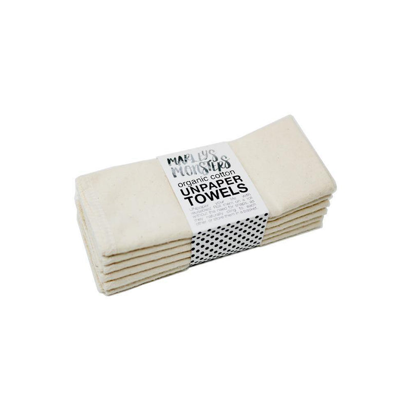 Product image of 6 natural white zero waste un paper towels stacked and wrapped in a recyclable craft paper sleeve.