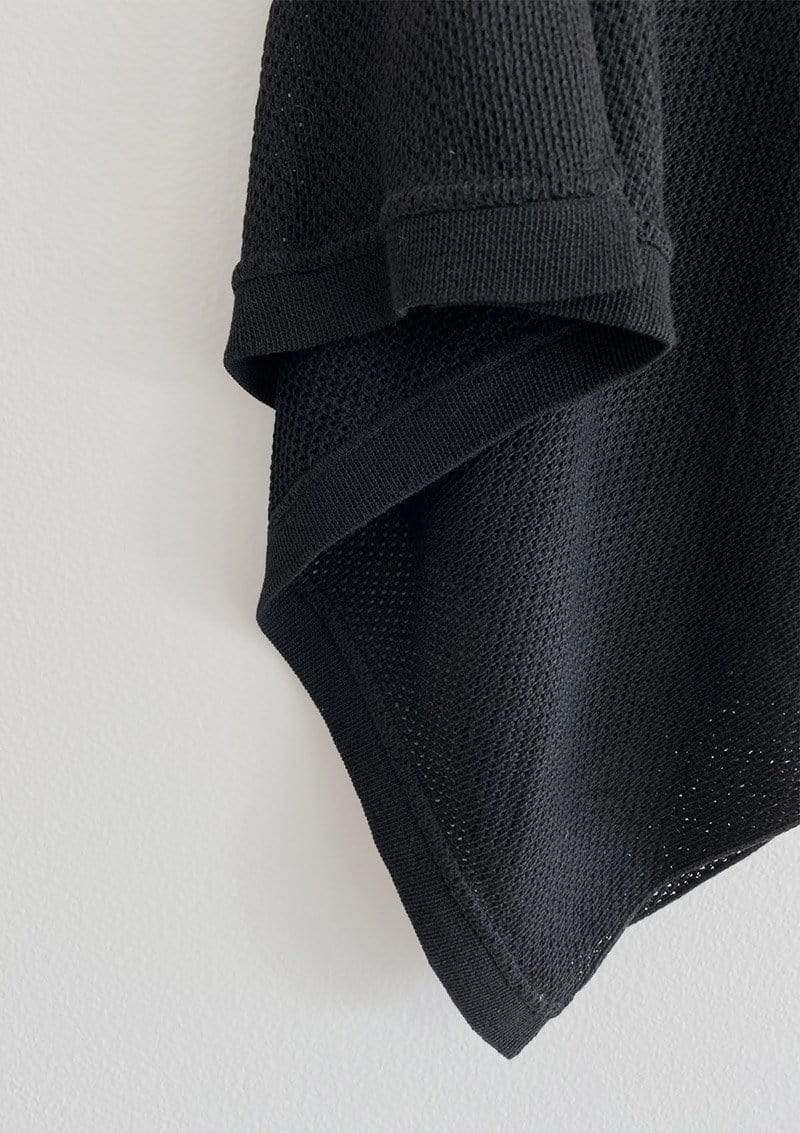Closeup of black knit Cocoon nursing cover showing breathable texture of knit and straight edge hem against white background