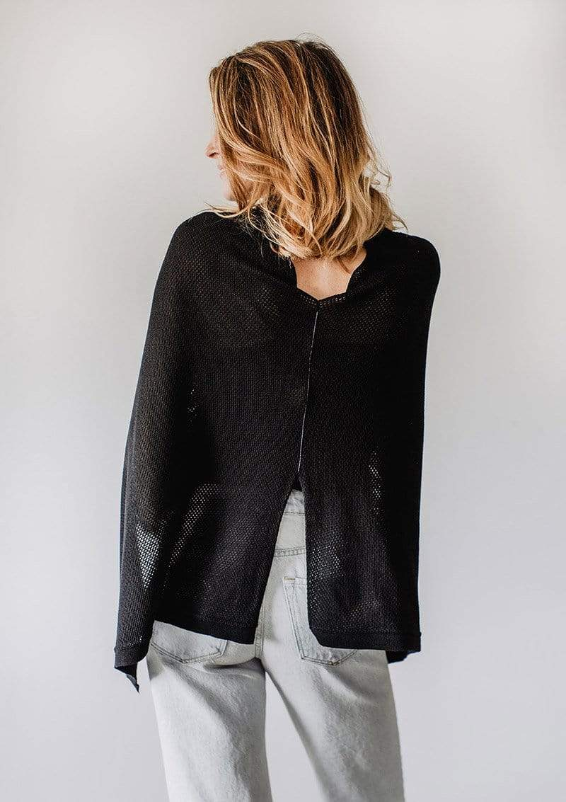 Back view of Emily Baldoni in a black knit Cocoon nursing cover worn as a cape with metallic black piping