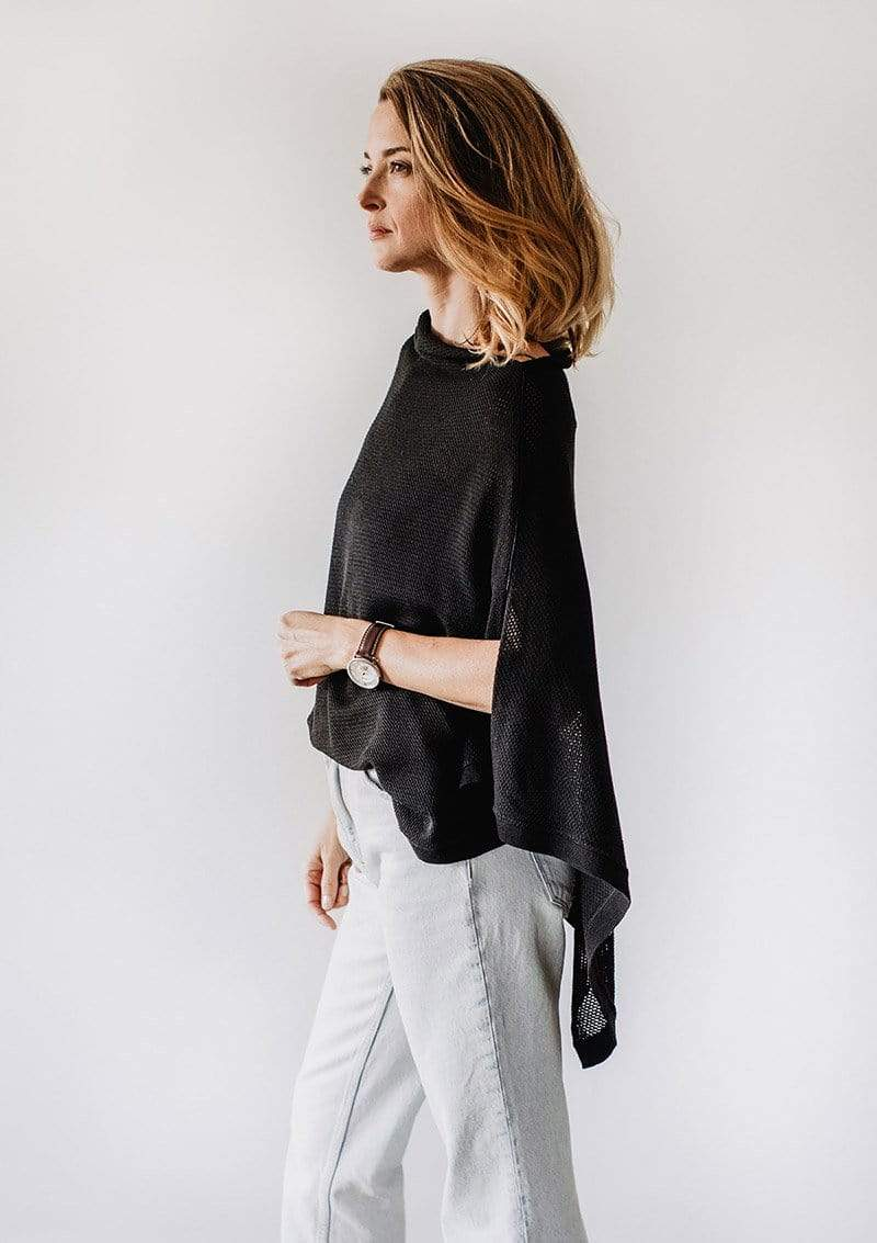 Side view of Emily Baldoni standing in a black knit Cocoon breastfeeding cover styled as a cape