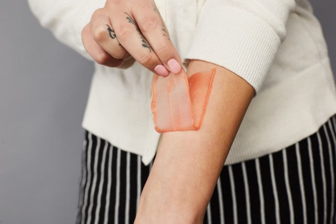 Woman pealing off the wax from her arm