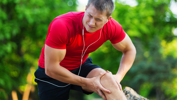 Male athlete with delayed onset muscles soreness, treating DOMS