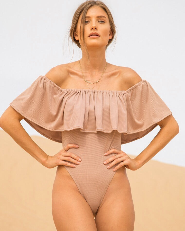 Our off the shoulder, seamless ruffle bodysuit with a thigh high cut, is a statement piece sure to turn heads. This piece can be worn with your favorite high waisted denim shorts or a flowy maxi skirt. With a lycra blend this bodysuit can also double as a swimsuit. One piece, ruffle top