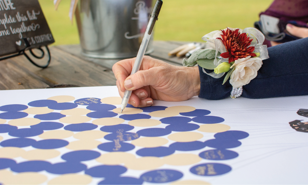 Close up of wedding guest signing on guest book alternative with balloons