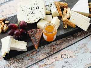 A plate of cheese and honey, fruit and nuts