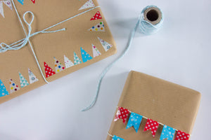 Two presents wrapped in brown kraft paper with colourful bunting tape edging