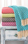 Five different colour throws neatly stacked on a rustic table