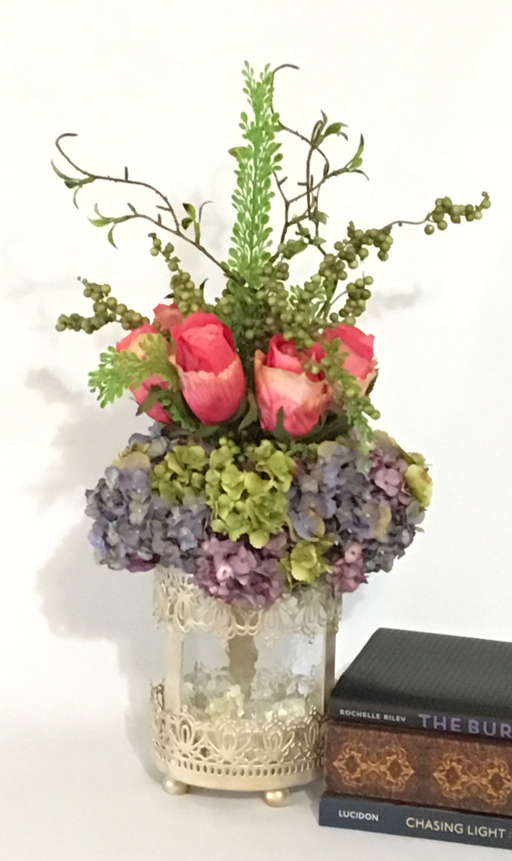 Hydrangeas & Roses product image.  Features purple green hydrangeas, barely opened pink roses, curly twigs in a soft crackled glass cylinder encased in a beautifully designed iron vase.  A single green orchid flower, visible through the glass cylinder sits on the bottom of the vase.  This arrangement is 21 inches high from top to bottom of the vase.