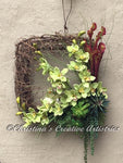 Nature's Blooms product image.  Features 22x22-inch grapevine framed wrapped in grapevine garland, light green cymbidium orchids, rust trumpet pitcher plants, green echeverias, cedar ferns, curly green twigs, Hanging strings of succulent pearls, light green and natural colored prairie bird.