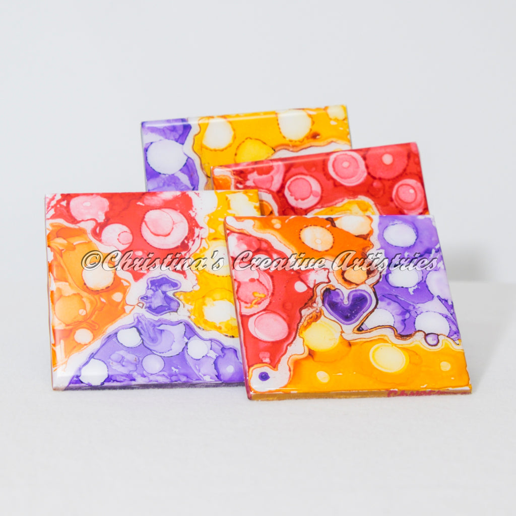 Gum Drops Ceramic Coasters proct image.  Features 4 x 4 hand-painted tile coasters. Colors yellow, purple, red and orange.  Set of 4.  Cork-backed.  Coaster stand included.