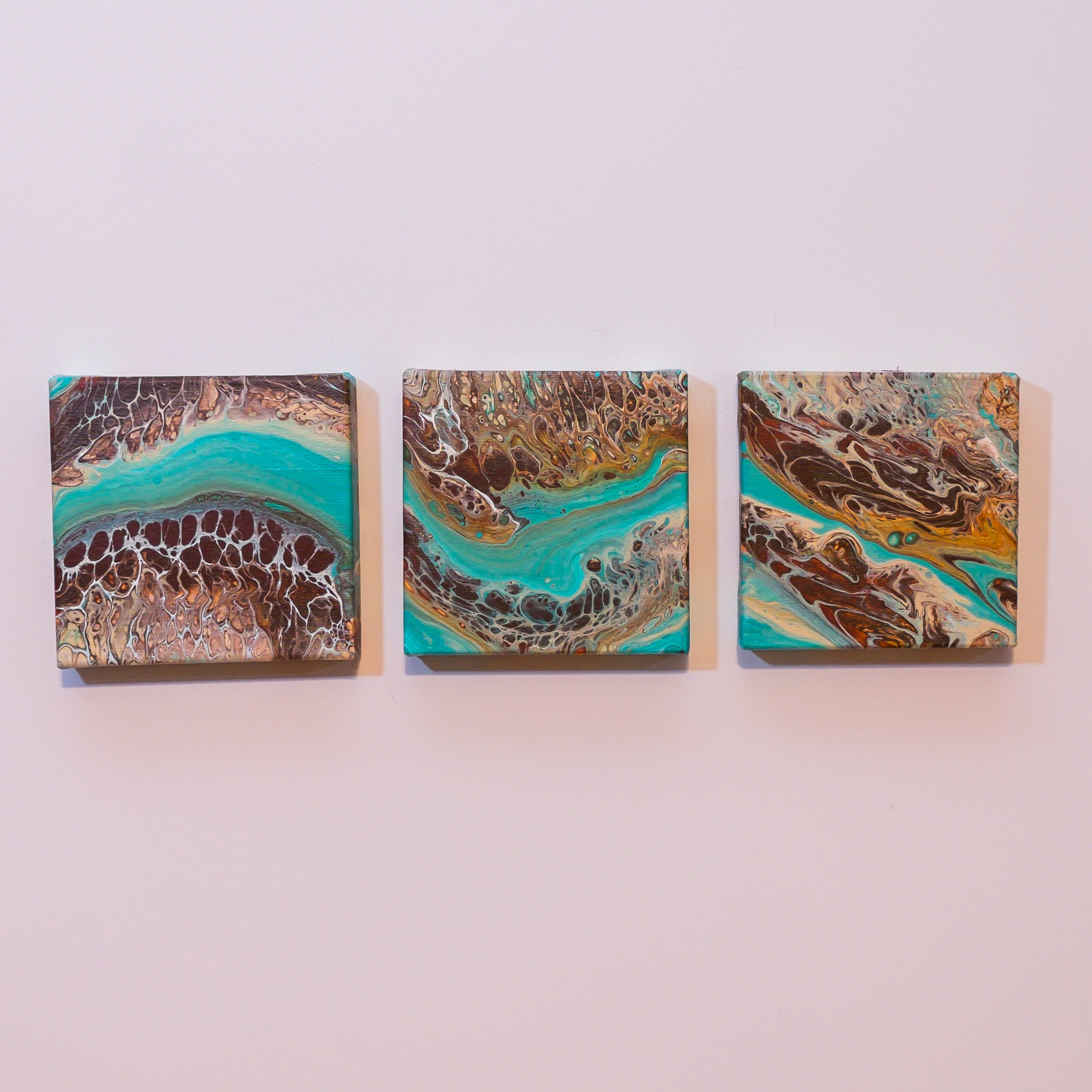 Rocky Bay Artwork by Christina Russell.  Image features a set of three. 6 x 6 inch gallery wrapped canvases. Fluid Art.  Acrylic Medium.  Colors are Teal, Tan and Amber.  Comes ready to hang.