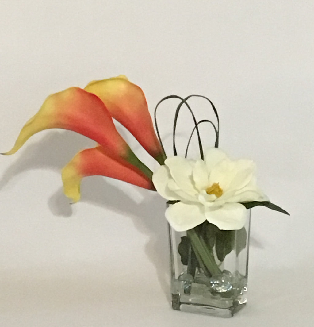"Magnolia and Calla Lillies product image.  Features 3 large orange yellow calla lilies, 1 Sweetbay magnolia, green bendable wire, iridescent marbles, acrylic water.  Vase is 6""x4""x3""."