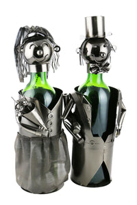 Bride & Groom Wine Bottle Buddies.  Features a bride in a metal mesh gown holding a bouquet and a man dressed in tux and top hat.  Bride and groom each hold a standard size, 750 ml wine bottle.  Bride and groom's head sit a top each bottle.