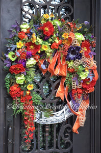 Beautiful Bettye product image features a 24 inch, whitewashed grapevine frame filled with mixed summer greenery and vibrant summer blooms in purples, citrus green,  orange and yellow.  This beautiful wreath made up with orchids, poppies, roses , ranunculuses and wisteria is embellished with a gorgeous triple bow in orange, purple and a natural open weave jute with loose loops and curly tails .   This wreath is finished at 26 inches in width by 32 inches from top to bottom.