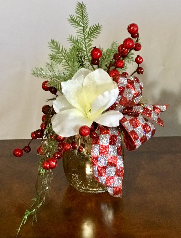 "Magnolia N Berries product image features mercury glass vase, cream magnolia, dark red berries, pine pick , dark red and silver checkered ribbon.  Measures 13""H x 10"" W.  Designer. Elegant tabletop decor.  Custom."