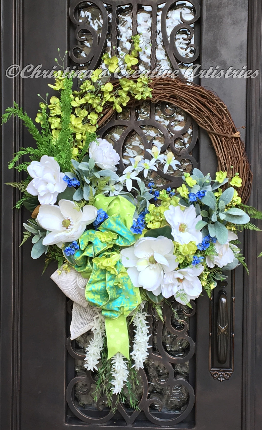 KarenChic wreath product image.  Features handcrafted 30-inches wide by 48-inches long by 12-inches deep.  White Magnolias, Lime green orchids, small blue blossoms, sedum ferns and mini light yellow blossoms, draping willow and white robinias. Triple bow with white burlap, tone on tone lime polka dots and a lime and blue poly silk.