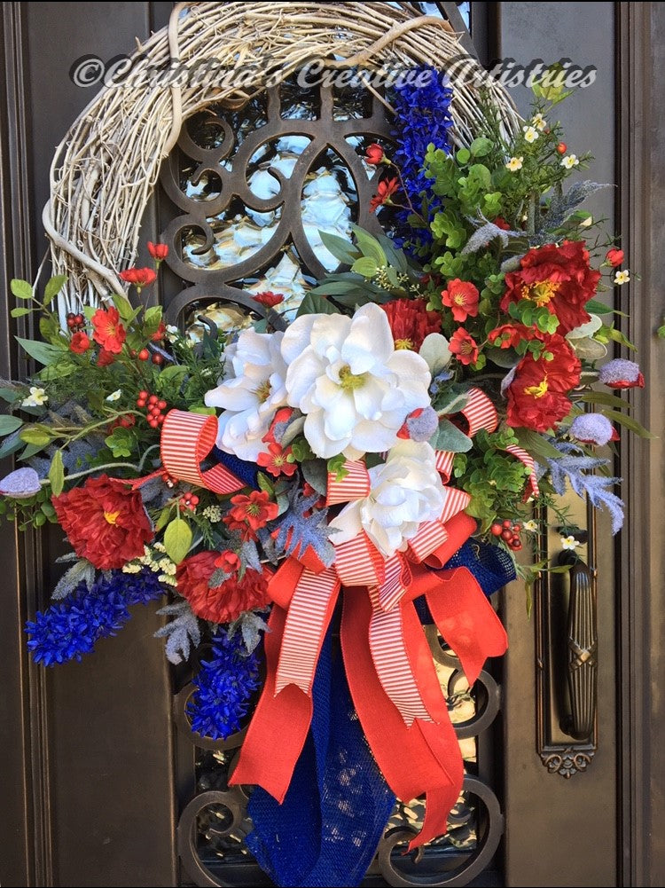 Summer Cotillion product image features 24 inch whitewashed grapevine frame, white magnolias, red poppies, blue liatris, red berries, mixed greenery accented with a triple bow made with a navy blue ribbon, a solid red ribbon and a red and white stripe ribbon.