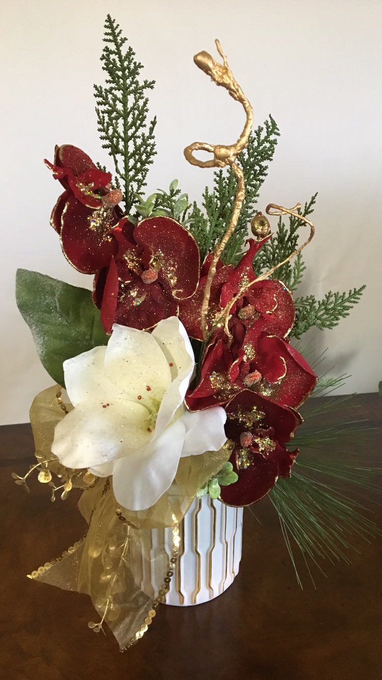 "Christmas Orchid features burgundy cascading orchids trimmed in gold, winter white magnolia, greenery, gold sheer ribbon, white modern vase.  Elegant. Christmas Decor.  Stunning Small Christmas Floral.  Measures 16""HX12""W.  Ideal for end table, coffee table, nightstand, bathroom countertop. Fabulous gift."