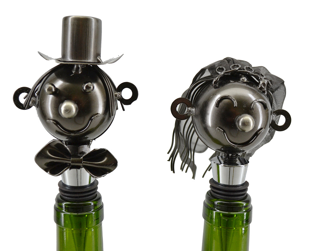 Bride and Groom Wine bottle stoppers.  Featuring a groom dressed in bowtie and top hat and a bride with a metal mesh vail on her head.