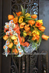 Orange and Yellow tulips, mixed greenery, leather fern picks, dried berries sprays and a gorgeous bow make up this elegant spring wreath.