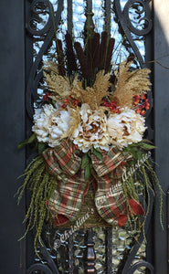 "Fall Basket features a natural ratan  basket,  filled with a layer of fall mums in cream, wheat pics and dark brown cattails.  A beautiful double bow with plaid in soft orange, olive, gold and teal is tied to top front portion of the basket.  Measures 31""hx16""w.  This is an elegant fall basket for a front or friends and family entryway."