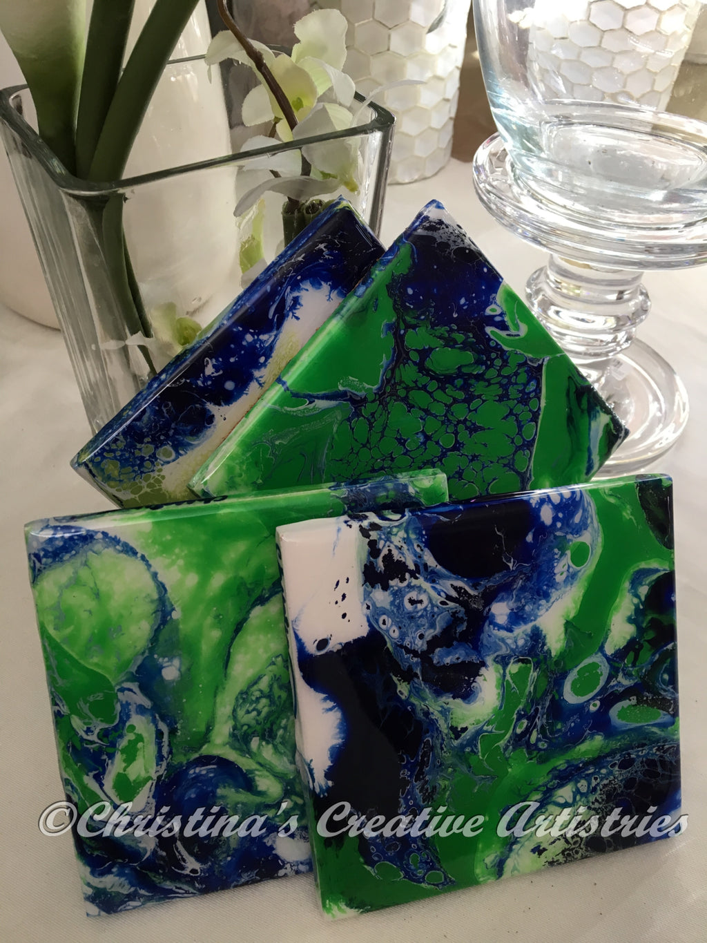 Power Fusion Ceramic Tile Coasters product image. Features 4 x4 inch ceramic tile coasters.  Handpainted.  Acrylics in navy blue and green on white background. Cork-backed. Durable coating. Sold as a set of 4.  Coaster stand included.