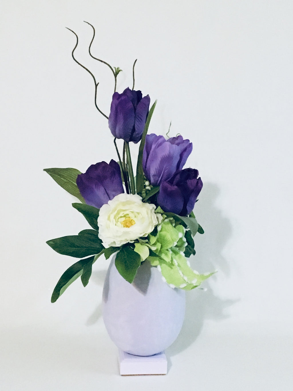 "Tulipapple Floral Bouquet product image features a beautiful floral arrangement made up with Tulips, peony, hydrangeas, greenery and curly twigs.  Colors are Lavender, white and apple green.  Measures 20"" high.  Tulipapple floral bouquet makes a great housewarming, teacher appreciation, hostess and Mother's Day gift.  Handmade Tulip bouquet. Spring Bouquet.  Tabletop decor."
