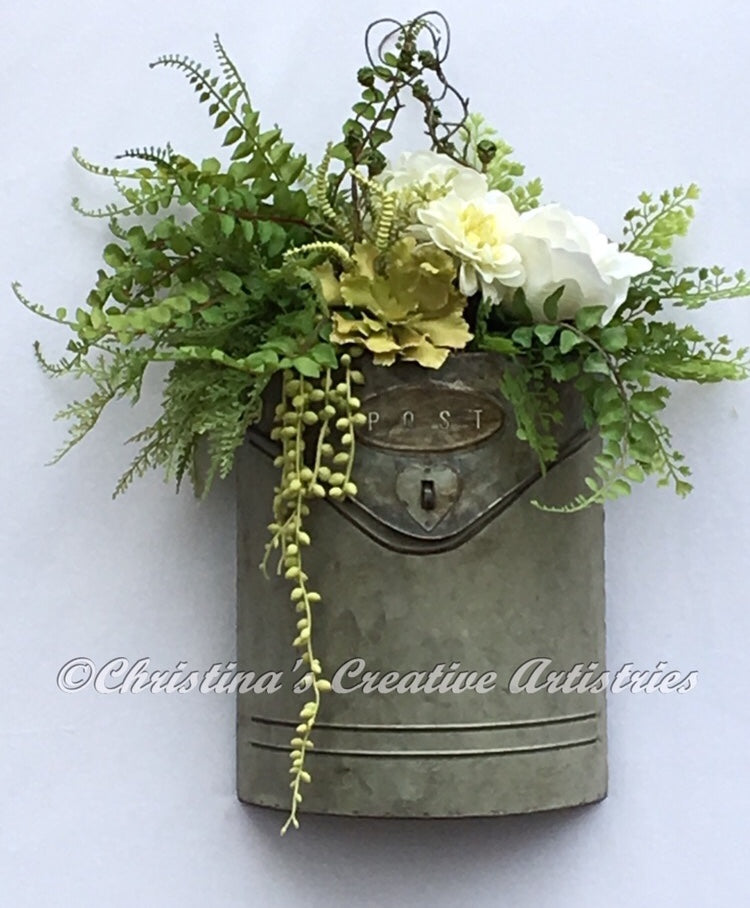 Mail Order product image.  Features a white open white rose, a green eichornia bokay, white hydrangea, white dahlia in a bed of button ferns, cedar ferns, maidenhair and finished with hanging succulent pearls.  A wire hanger is attached to the back of the box for hanging.  Hang in a covered area.