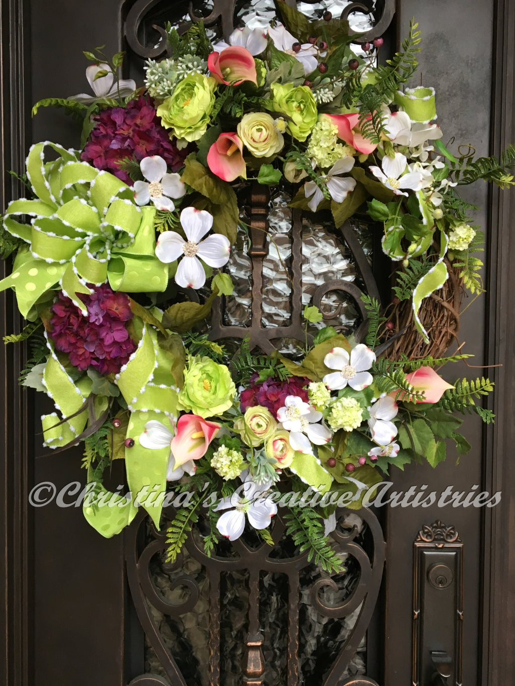 Christina's Creative Artistries' Glorious Spring product image. A gathering of silk magenta hydrangeas, pink calla lilies, lime green ranunculuses, white dogwood, ferns and lime green bow on a grapevine frame.