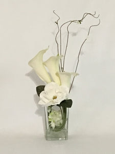 Calla Lilies and Magnolia product image.  Features 3 large white Calla Lilies, curly willow stems, Sweetbay magnolia and small white orchids in a 6-inch high modern proportion clear rectangular vase with acrylic water and iridescent marbles.
