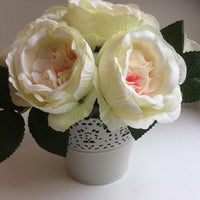 a bunch of cream and pink roses