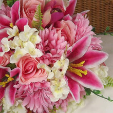 a brides bouquet of pink and ivory hydrangea, lily, gerbera and roses