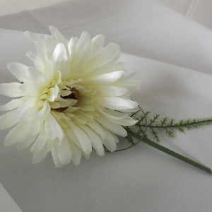 an artificial wedding buttonhole featuring an ivory silk gerbera