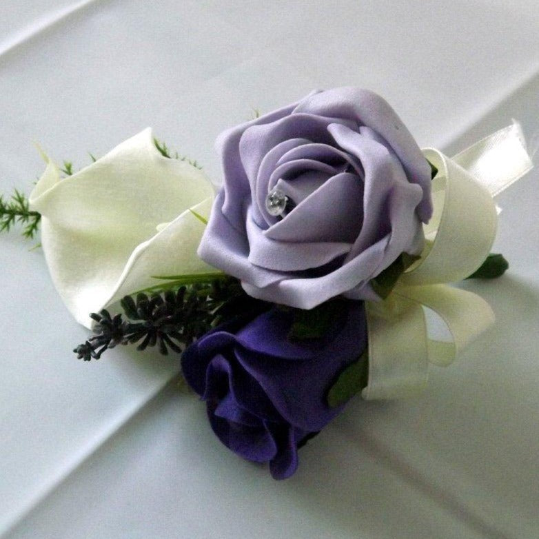 an artificial wedding corsage of ivory & purple foam roses plus calla lily