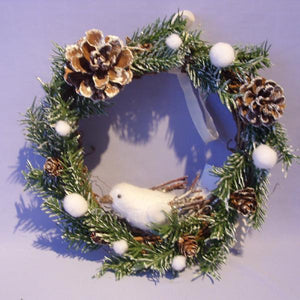 A frosty christmas wreath of artificial fir branches and pinecones with white dove.