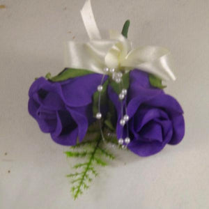 wedding buttonhole features two purple foam roses